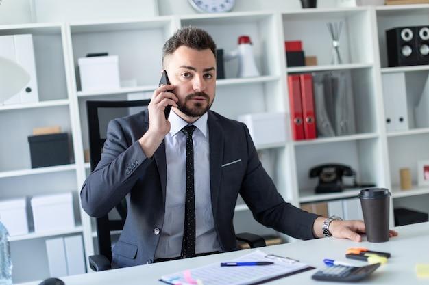 Um homem está sentado à mesa do escritório, falando ao telefone e segurando um copo de café.