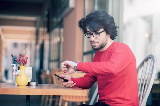 Um homem está sentado em um café e olha a hora