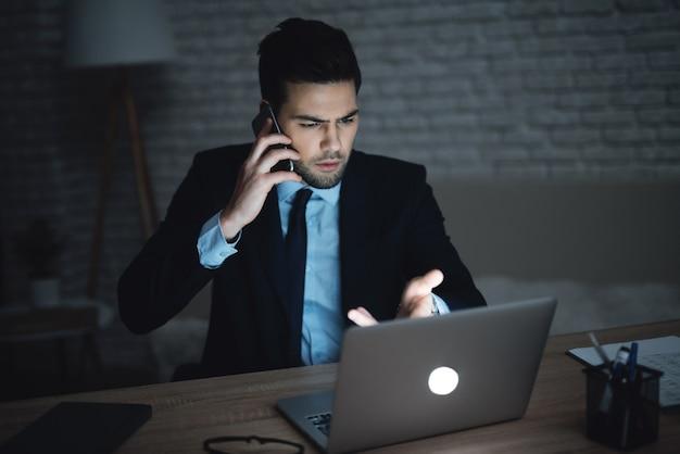 Um homem está sentado em um laptop em um escritório escuro.