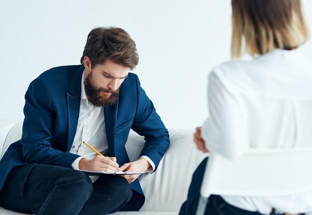Um homem está sentado em um sofá ao lado de um paciente visitando um psicólogo, uma terapia de problemas
