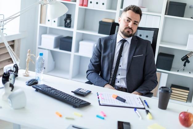 Um homem está sentado em uma cadeira no escritório à mesa.