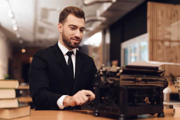 Um homem está sentado em uma mesa com uma velha máquina de escrever.