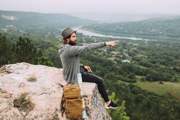 Um homem está sentado na beira de um penhasco e mostra a distância.