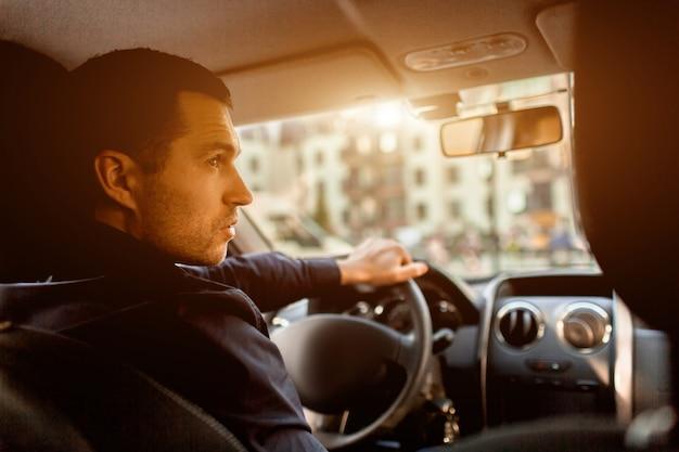 Um homem está sentado na cabine de um carro e olha para a rua
