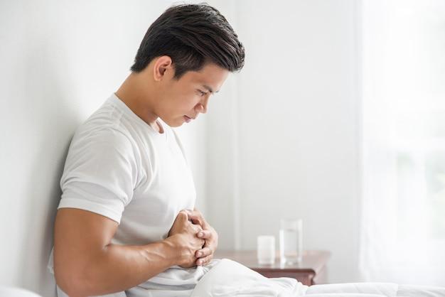 Um homem está sentado na cama com dor de estômago e pressiona o estômago com as mãos.