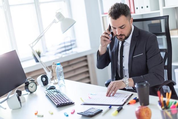 Um homem está sentado no escritório à mesa, falando ao telefone e folheando os documentos.