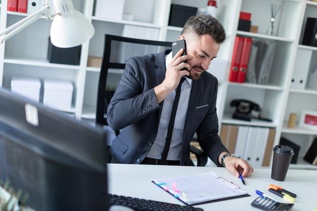 Um homem está sentado no escritório à mesa, falando ao telefone e trabalhando com documentos.