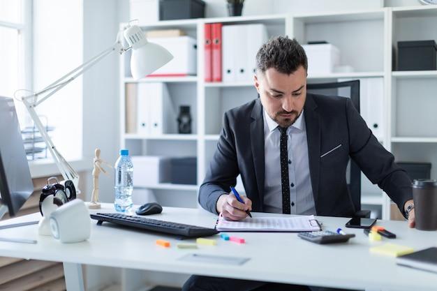 Um homem está sentado no escritório à mesa, segurando um copo de café e uma caneta na mão e trabalhando com documentos