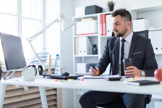 Um homem está sentado no escritório à mesa, segurando um marcador e um copo de café na mão e olhando para o monitor.