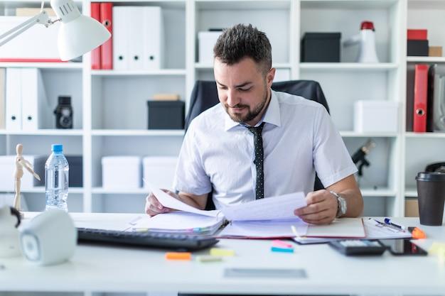 Um homem está sentado no escritório e trabalhando com documentos