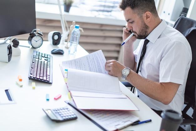 Um homem está sentado no escritório, trabalhando com documentos, segurando um marcador na boca e falando ao telefone.