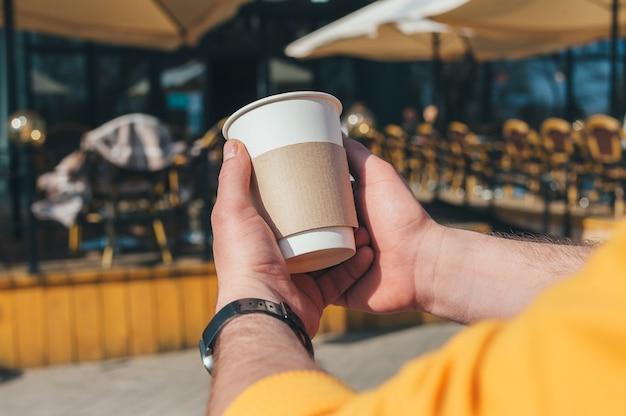 Um homem está tomando café em um restaurante ao ar livre.