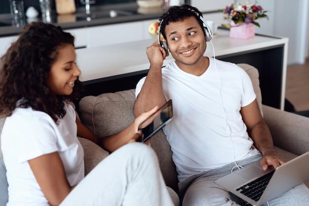Um homem está trabalhando em um laptop com a namorada.