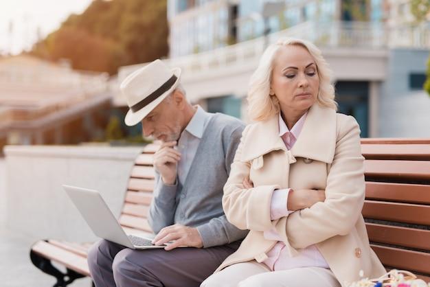 Um homem está trabalhando em um laptop, uma mulher está ofendida com ele