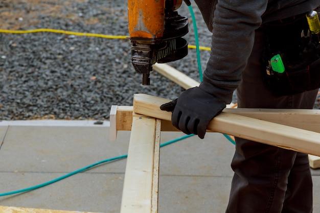Um homem está trabalhando na construção de uma parede de uma casa. ele está em uma escada horizontalmente emoldurado tiro.