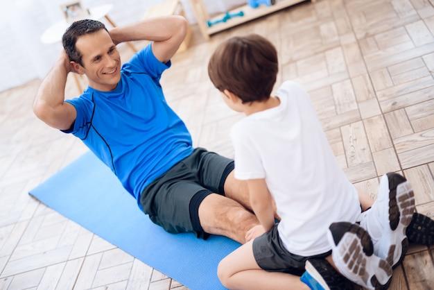 Um homem está treinando uma imprensa com a ajuda de um menino.