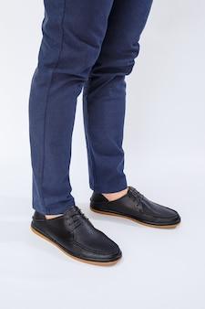 Um homem está usando sapatos pretos clássicos feitos de couro natural com renda, sapatos masculinos no estilo empresarial
