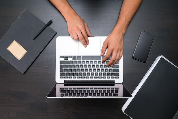 Um homem está usando um computador laptop na mesa de madeira vintage.
