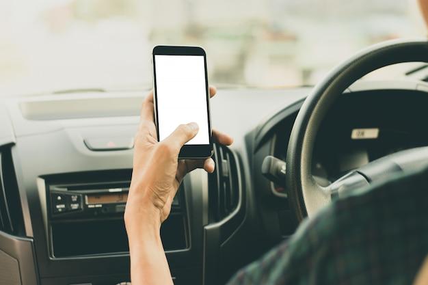 Um homem está usando um smartphone com uma tela em branco enquanto dirige um carro