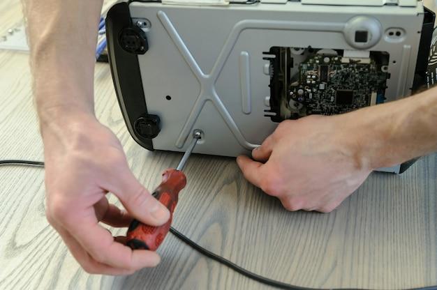 Um homem está usando uma chave de fenda para abrir o sistema de música.