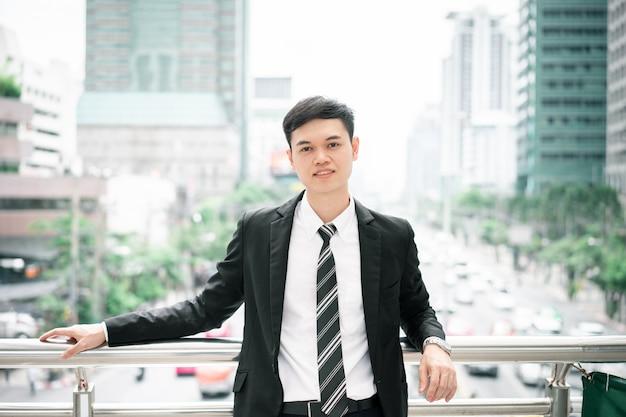 Um homem está vestindo um terno preto, camisa branca e gravata.