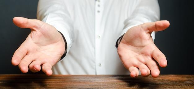 Um homem estende as mãos em uma expressão emocional de espanto. mostre a causa do sofrimento
