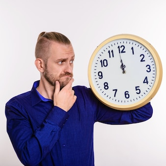 Um homem estiloso pensa na ideia e segura um grande relógio de parede branco