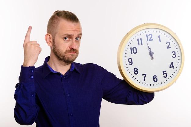 Um homem estiloso segura um grande relógio de parede e aponta o dedo sobre o branco