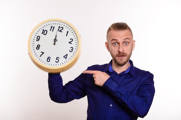 Um homem estiloso segura um grande relógio de parede nas mãos e aponta para eles com o dedo no branco