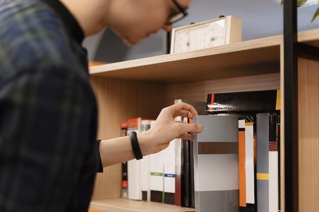 Um homem estudante escolhendo livros da prateleira