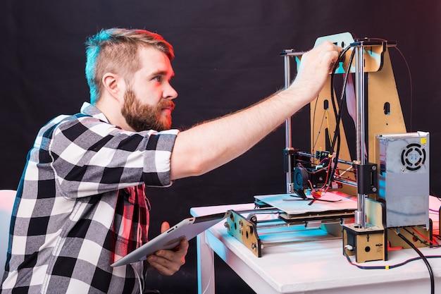 Um homem estudante imprime protótipo na impressora.