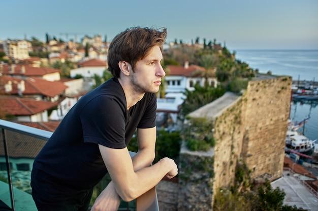Um homem europeu esguio com cerca de anos de idade olha tristemente para a cidade velha de antalya de um ponto de observação