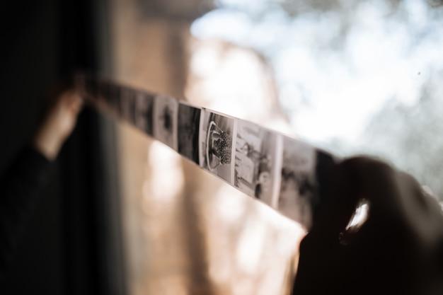 Um homem examina um filme de formato médio contra uma janela. vintage velho