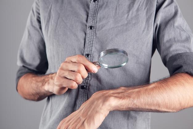 Um homem examina uma mão com uma lupa