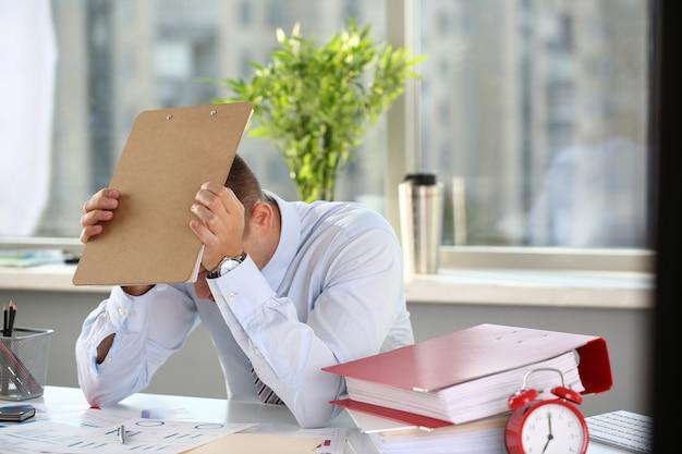 Um homem experimenta estresse e prancheta de dor de cabeça