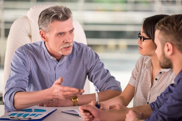 Um homem explica algo aos seus colegas no trabalho.