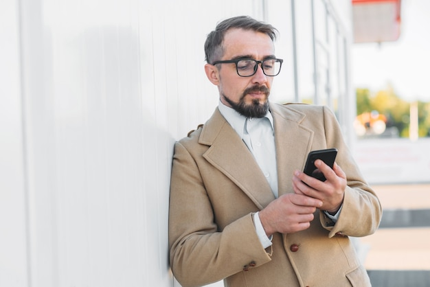 Um homem fala ao telefone - close-up em uma cidade branca.