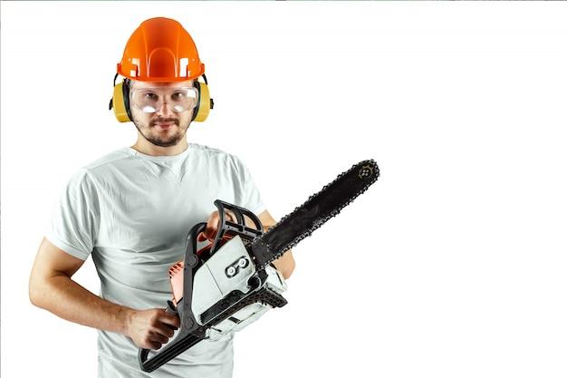 Um homem farpado em um capacete que guarda uma serra de cadeia em um fundo branco.