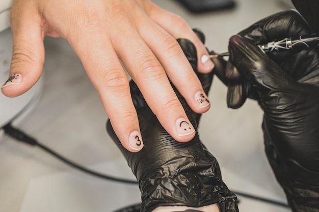 Um homem faz as unhas. coloração de unhas masculinas. projeto de manicure masculina. mulher aplicando esmalte preto na mão do homem, close-up tiro.