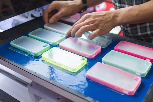 Um homem faz o caso do smartphone para a máquina de impressão. inovação da capa e design móveis.