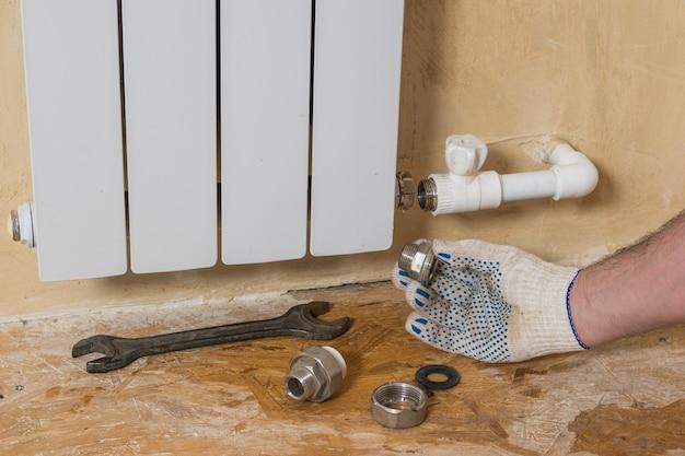 Um homem faz reparos no sistema de aquecimento de uma casa particular. acidente do sistema de aquecimento de uma casa privada. radiador de aquecimento.