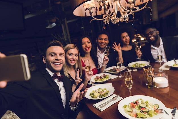 Um homem faz selfies com amigos no restaurante.