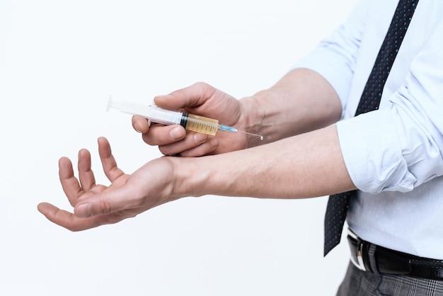 Um homem faz uma injeção na mão.