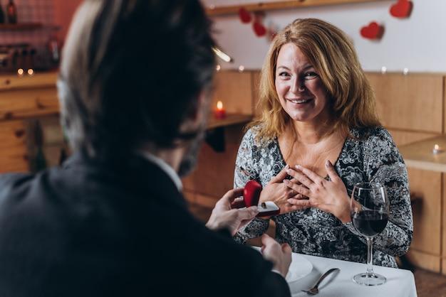 Um homem faz uma proposta de casamento para uma mulher de meia idade no jantar. mulher, surpreendido