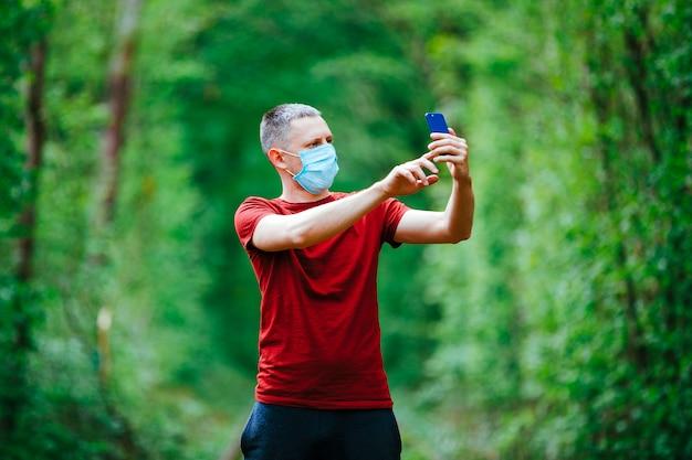 Um homem faz uma selfie em uma máscara em um fundo de floresta