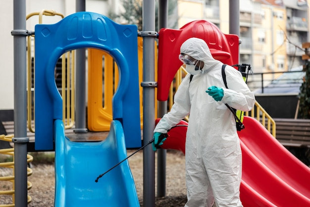 Um homem fazendo um ótimo trabalho com roupas de proteção brancas esteriliza um escorregador em um parquinho infantil. as crianças são a prioridade número um. situação de surto de coronavírus, fique seguro