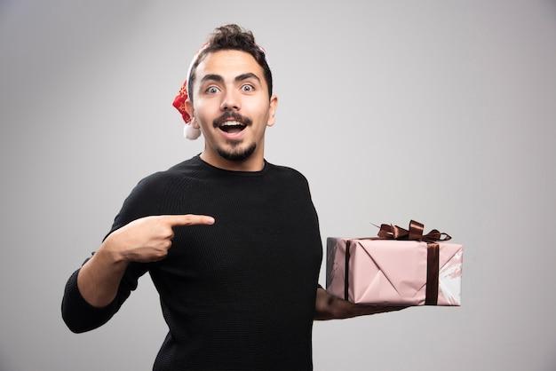 Um homem feliz com um chapéu de papai noel, apontando para um presente.