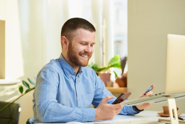 Um homem feliz com uma barba de camisa azul rindo e segurando nas mãos um cartão de crédito e um smartphone na frente do computador em casa