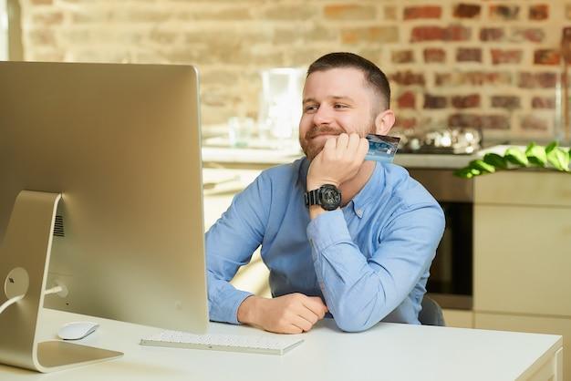Um homem feliz com uma barba espera na frente do computador e tem um cartão de crédito em casa