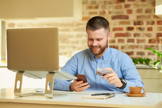 Um homem feliz com uma barba usando um smartphone com um cartão de crédito na mão na frente do computador em casa